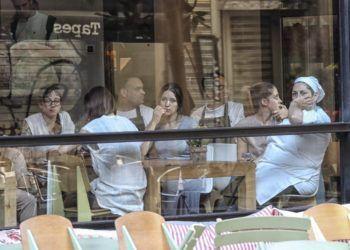 Varias personas esperan en el interior de un bar la autorización de la policía para poder salir. Foto: Joan Sánchez.