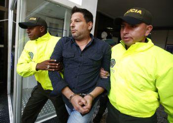El cubano Raúl Gutiérrez conducido por dos policías tras su detención en Colombia en 2018, acusado de planear acciones terroristas. Foto: Fernando Vergara / AP / Archivo.