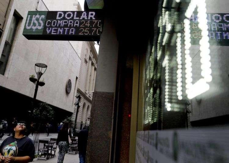 Una mujer observa una pantalla con las tasas de cambio entre el peso argentino y el dólar estadounidense en Buenos Aires, el martes 15 de mayo de 2018. Foto: Natacha Pisarenko / AP.