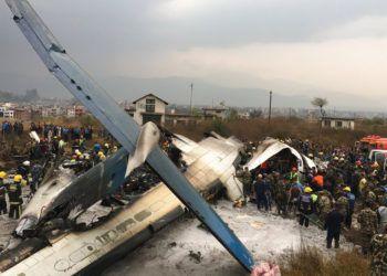Rescatistas nepalíes junto a un avión de pasajeros de Bangladesh estrellado en el aeropuerto de Katmandú, en Nepal. Foto: Niranjan Shreshta / AP.