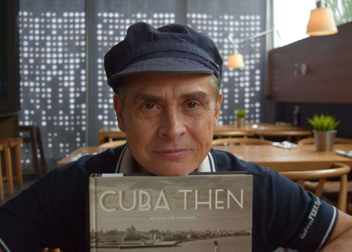 """El coleccionista de fotos de Cuba Ramiro A. Fernández posando junto a su libro """"Cuba Then"""" durante una entrevista con Efe. Foto: Jorge Ignacio Pérez / EFE."""