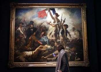 """Una mujer mira la pintura """"La liberté guidant le peuple"""" de Eugène Delacroix en el Museo del Louvre en París. Foto: Christophe Ena / AP."""