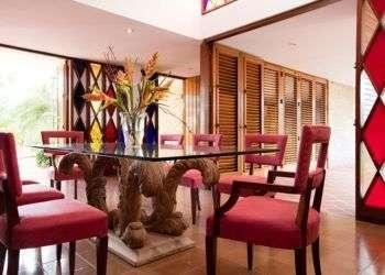 Los propietarios Nora Belanzauran y Otto Hermos mantuvieron la mesa de estilo barroco de la década de 1950 y las sillas en suite en una casa de mediados de siglo diseñada por el maestro moderno Frank Martínez. Las persianas de madera y vidrieras de colores son características de la arquitectura de estilo moderno tropical. Foto: Alain Gutiérrez.