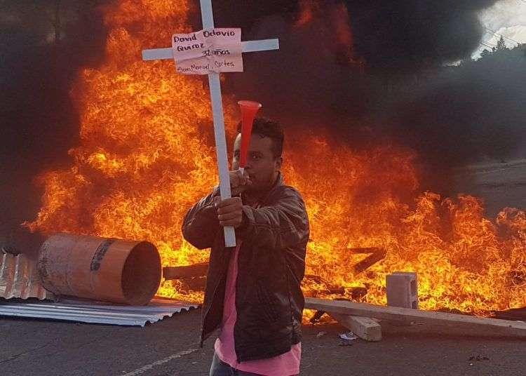 Manifestante muestra una cruz con el nombre de una de las víctimas de las represiones militares. Inicia la movilización de protesta contra toma de posesión de Juan Orlando Hernández. Foto: Twitter de Gilda Silvestrucci, Corresponsal en Honduras de Telesur.