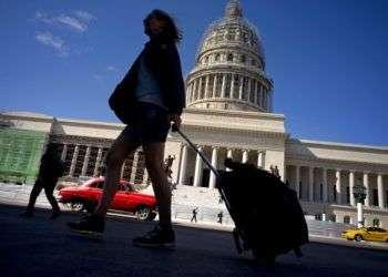 Una turista camina con su maleta por delante del Capitolio, en La Habana, Cuba. Foto: Ramón Espinosa / AP.