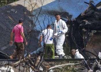 Forenses y agentes del ministerio del Interior remueven los restos de un Boeing 737 que cayó en un campo de yuca con más de 100 personas a bordo poco después de despegar de La Habana, Cuba, 18 de mayo de 2018. Foto: Desmond Boylan/AP.