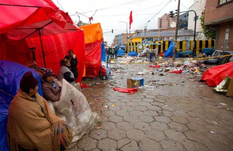 Vendedores callejeros cerca del lugar donde explotó un cilindro de gas en Oruro, Bolivia, que provocó ocho fallecidos y 40 heridos. Foto: Juan Karita / AP.