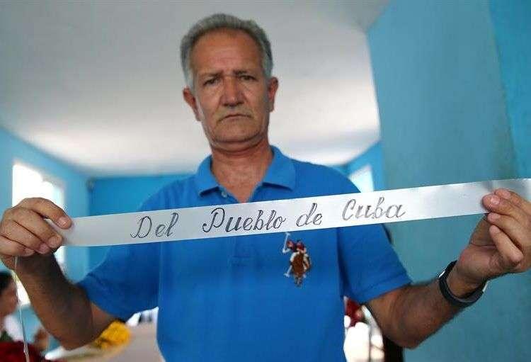 El profesor Carlos Parra rotula cuidadosamente dedicatorias en las coronas que acompañan las urnas de los fallecidos en el desastre aéreo que el viernes pasado enlutó la provincia cubana de Holguín, que perdió 67 hijos en el siniestro. Foto: Alejandro Ernesto/EFE.