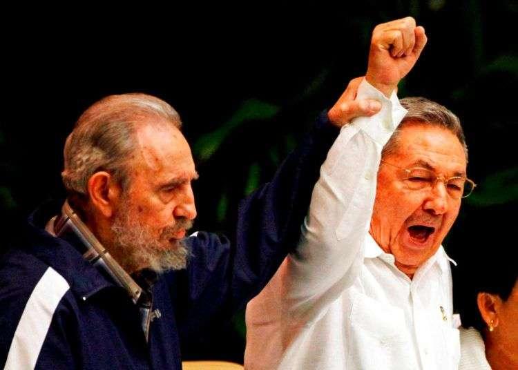 Fidel Castro levanta la mano de su hermano Raúl Castro, mientras cantan el himno de la internacional socialista durante el VI Congreso del Partido Comunista en La Habana, el 19 de abril de 2011. Foto: Javier Galeano / AP/Archivo.