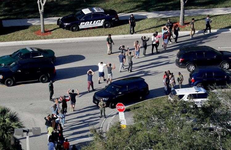 Estudiantes salen con las manos arriba de la escuela secundaria Marjory Stoneman Douglas, en Florida, después del tiroteo del pasado 14 de febrero. Foto: Mike Stocker / South Florida Sun-Sentinel vía AP.
