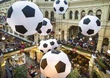 Turistas y aficionados del fútbol caminan por el centro comercial GUM decorado con enormes balones de fútbol con motivo del Mundial en Moscú, Rusia. Foto: Alexander Zemlianichenko/AP.