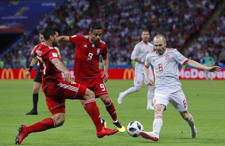 El español Andrés Iniesta (derecha) pugna por un balón con Omid Ebrahimi (centro) y Masoud Shojaei, de Irán, este miércoles 20 de junio de 2018 en Kazán, Rusia. Foto: Manu Fernández / AP.
