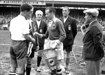 El futbolista cubano Manuel Chorens saluda al rumano Gheorghe Rasinaru frente a los árbitros, antes del inicio de uno de los partidos entre Cuba y Rumanía en el Mundial de Francia 38. Foto: goal.com