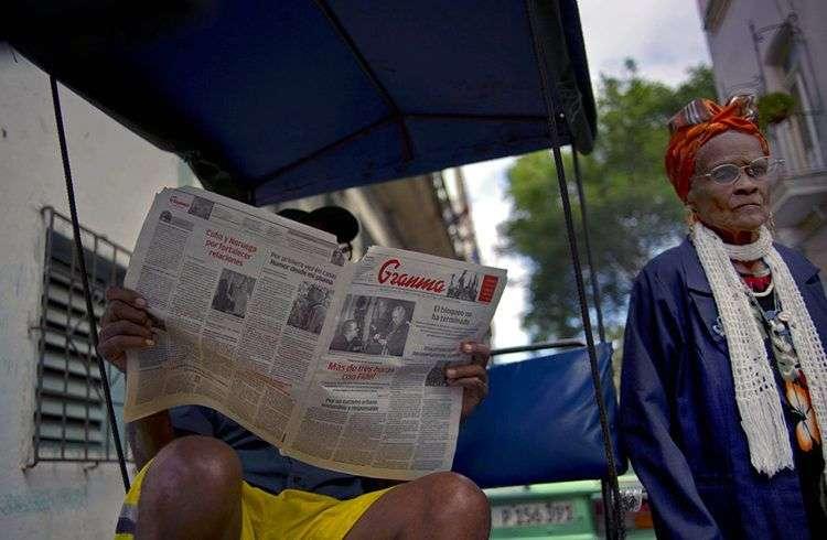En esta imagen de archivo, tomada el 3 de febrero 2015, un hombre lee un ejemplar de Granma, diario oficial del Comité Central del Partido Comunista de Cuba, mientras una mujer pasa por su lado, en La Habana vieja. Foto: Ramon Espinosa / AP / Archivo.