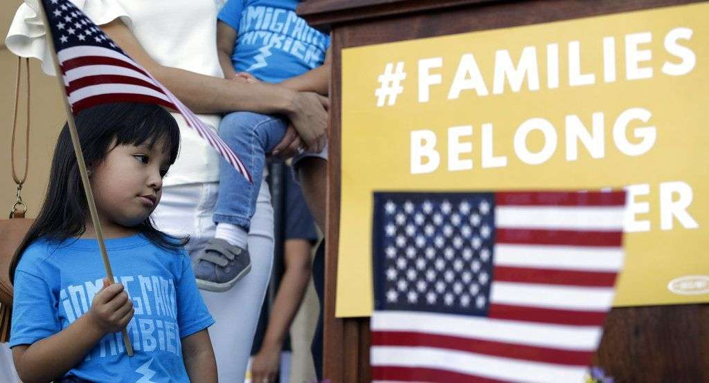 Andrea Elena Castro, hija del representante demócrata Joaquin Castro, sostiene una bandera durante un evento para protestar por la nueva política migratoria que ha derivado en la separación de familias, el jueves 31 de mayo de 2018, en San Antonio. Foto: Eric Gay / AP.