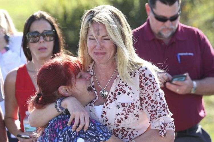 Padres esperan por noticias tras el reporte de un tiroteo en la Escuela Secundaria Marjory Stoneman Douglas de Parkland, Florida. Foto: Joel Auerbach / AP.