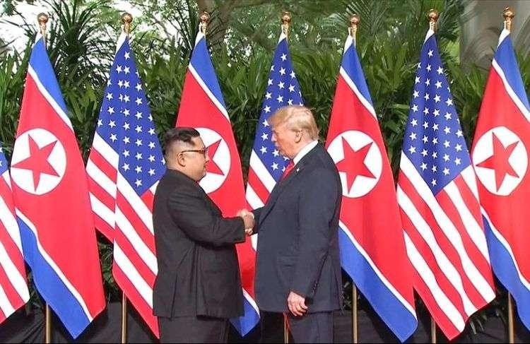 Donald Trump y al mandatario norcoreano Kim Jong Un se estrechan la mano antes del inicio de su reunión en el Hotel Capella de Singapur este martes 12 de junio de 2018. Imagen tomada del video de Host Broadcaster Mediacorp Pte Ltd vía AP.