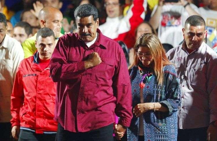 El presidente de Venezuela, Nicolás Maduro, se lleva el puño al corazón a su llegada, acompañado por su esposa Cilia Flores, a un acto con seguidores después de su reelección para un segundo mandato en las elecciones presidenciales, en Caracas, Venezuela, el 20 de mayo de 2018. Foto: Ariana Cubillos/AP.