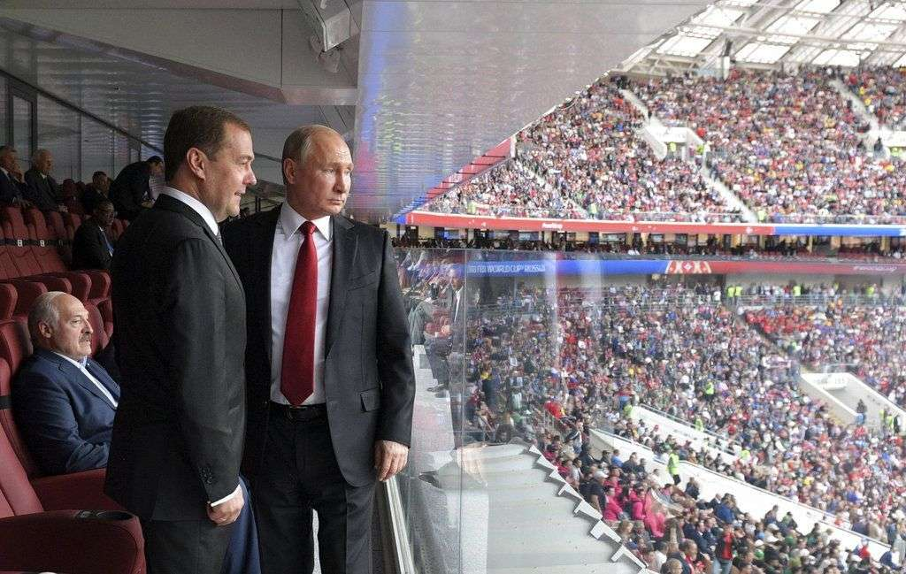 Russian President Vladimir Putin and Russian Prime Minister Dmitri Medvedev watching the field during the Russia-Saudi Arabia game that started off the 2018 World Football Championship in Moscow's Luzhinski Stadium, on June 14, 2018. Photo: Alexei Druzhinin / Sputnik / Kremlin Photo Pool via AP.