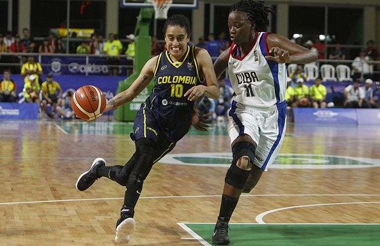 La jugadora de Colombia Mabel Martínez (izq) disputa el balón con la cubana Marlene Cepeda en la final de baloncesto femenino en los Juegos de Barranquilla. Foto: Luis Eduardo Noriega / EFE.