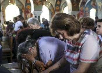 Fieles ortodoxos asisten a un funeral por las víctimas de un incendio, dentro de una iglesia en la localidad de Mati, al este de Atenas, el 29 de julio de 2018. Foto: Yorgos Karahalis/AP.