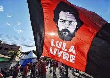 Un partidario del expresidente Luiz Inácio Lula da Silva ondea una bandera con la imagen del exmandatario frente a los cuarteles de la policía federal donde Lula cumple una sentencia de 12 años de prisión, el domingo 8 de julio de 2018. Foto: Denis Ferreira Netto / AP.