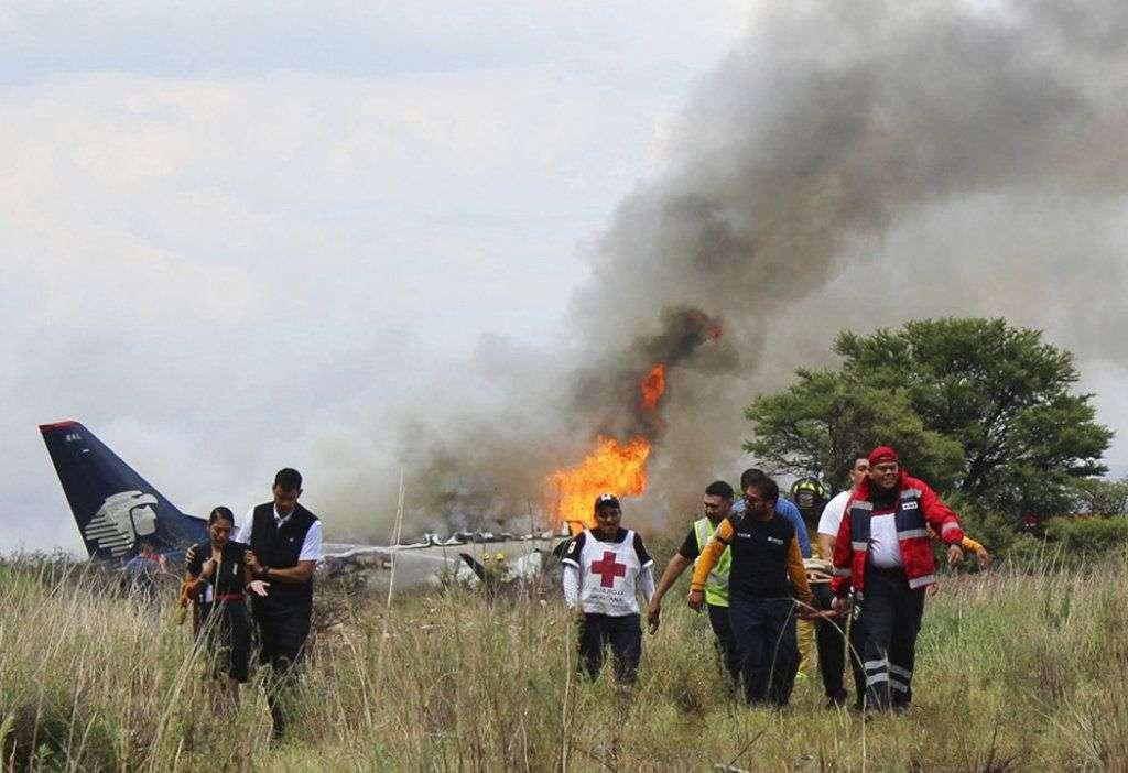 Miembros de la Cruz Roja y rescatistas llevan a una persona herida en una camilla luego del desplome de un avión comercial de Aeroméxico en las inmediaciones del aeropuerto de Durango, México, el martes 31 de julio de 2018. Foto: Cruz Roja de Durango vía AP.
