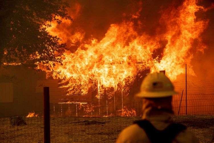 Un bombero controla un edificio en llamas para asegurarse de que no se expandan mientras el incendio River calcina parte de la ciudad de Lakeport, en California, el 30 de julio de 2018. Foto: Noah Berger / AP.