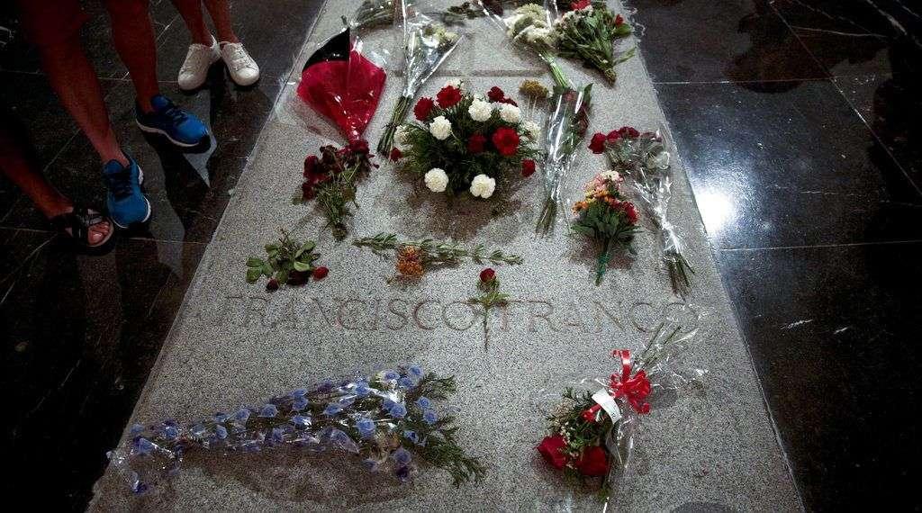 Varias personas, de pie junto a la tumba del ex dictador Francisco Franco, en el interior de la basílica del Valle de los Caídos, en El Escorial, a las afueras de Madrid. Foto: Andrea Comas / AP.
