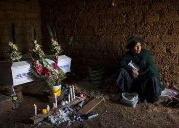 En imagen del 15 de agosto de 2018, Marta Tineo Espinosa se sienta al lado de los féretros de sus parientes, que murieron a manos del grupo armado Sendero Luminoso y el ejército peruano en 1984, en el día de su entierro en Tantana, en la provincia de Ayacucho, Perú. Foto: Rodrigo Abd / AP.
