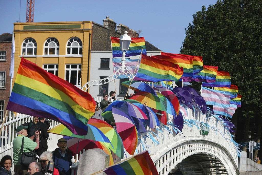 Banderas de arcoiris y cintas azules ondean con el aire en el puente Ha'Penny, en Dublín, para recordar a las víctimas de abuso sexual por parte de los clérigos de la Iglesia católica, antes de la llegada del papa Francisco Dublín, Irlanda, el sábado 25 de agosto de 2018. Foto: Niall Carson/PA/AP.