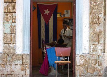 Un barbero rasura a un cliente en su negocio privado en La Habana, Cuba, el martes 10 de julio de 2018. Foto: Desmond Boylan / AP.