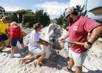 Walker Townsend (derecha), de Isle of Palms, en Carolina del Sur, llena un saco de arena que sostiene Dalton Trout, en un estacionamiento municipal donde se reparte arena de forma gratuita dentro de los preparativos para la llegada del huracán Florence a la región. Foto: Mic Smith / AP.