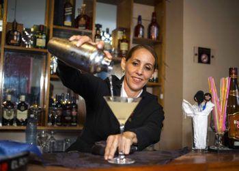La cantinera cubana Bárbara Betancourt sirve un daiquiri en un bar de La Habana. Foto: Desmond Boylan / AP.
