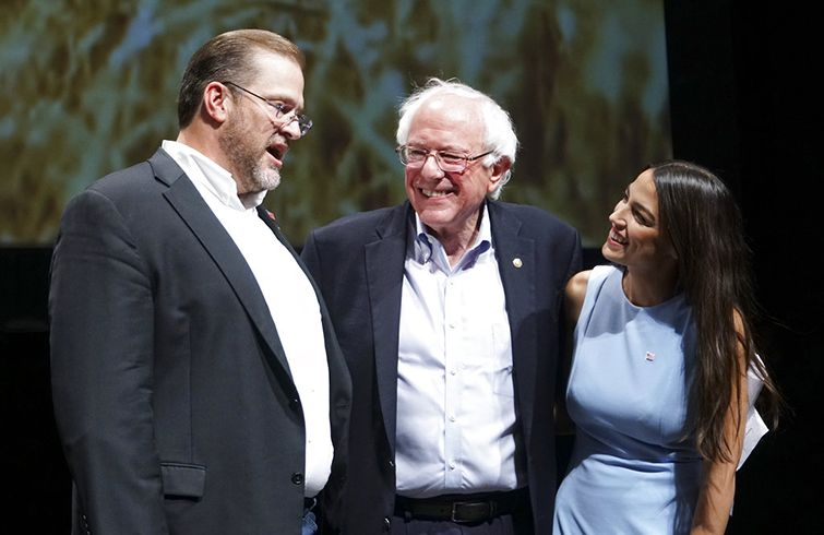 Alexandria Ocasio-Cortez junto a Bernie Sanders (centro) y al candidato demócrata a representante James Thompson en un acto en Wichita, Kansas, en julio del 2018. Foto: Jaime Green / The Wichita Eagle vía AP / Archivo.