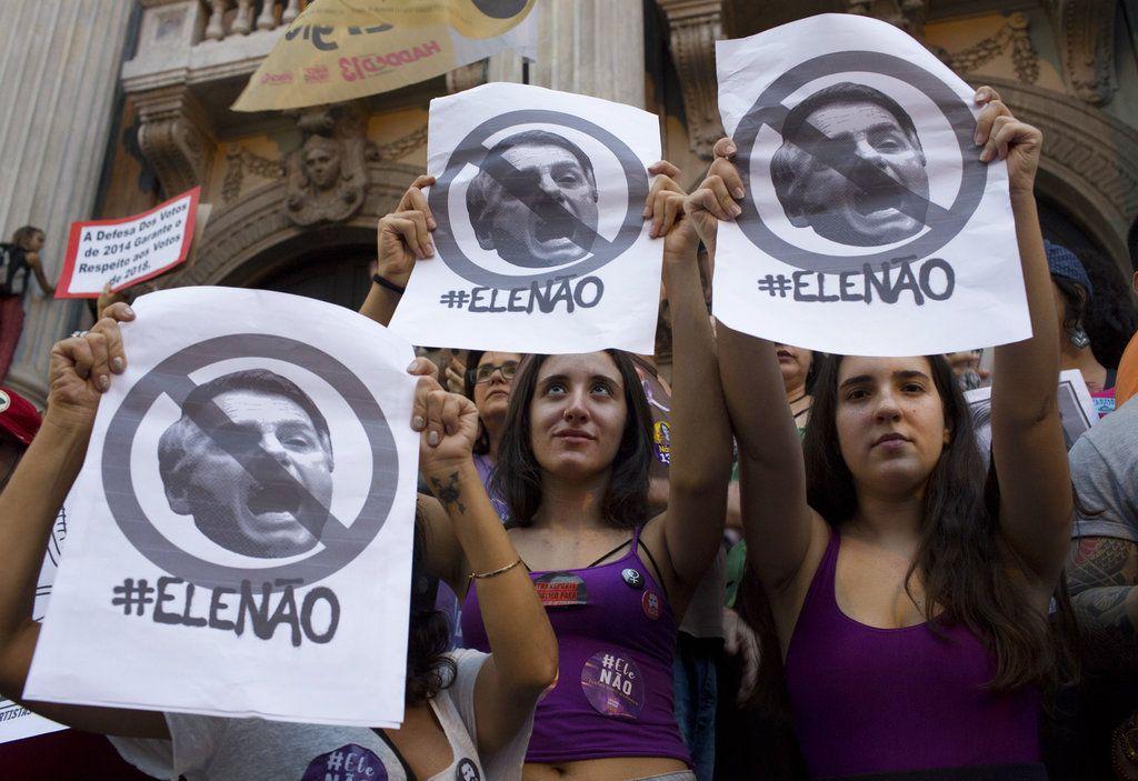 """Mujeres muestran carteles con la frase """"Él no"""" durante una protesta contra el candidato a la presidencia Jair Bolsonaro. Foto: Silvia Izquierdo/AP."""