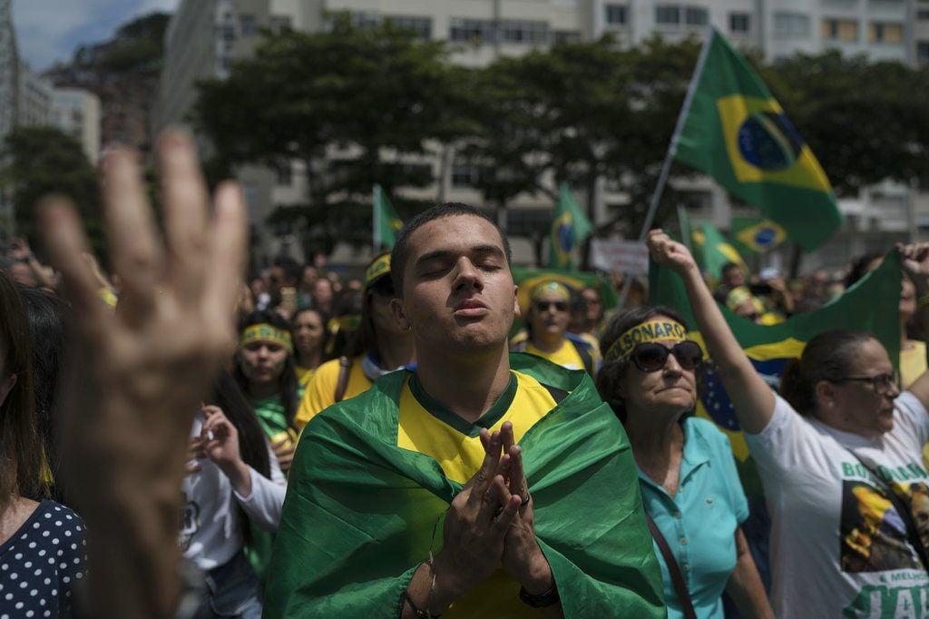Una multitud escucha el himno nacional en el acto de campaña del candidato presidencial ultraderechista Jair Bolsonaro en Río de Janeiro, Brasil, el domingo 21 de octubre de 2018. Foto: Leo Correa / AP.