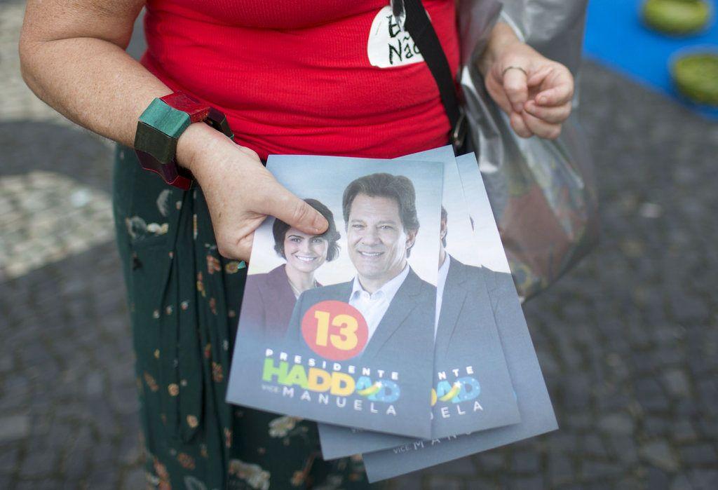 En esta imagen del 17 de octubre, una voluntaria de campaña sostiene volantes a favor del candidato del Partido de los Trabajadores, Fernando Haddad, y utiliza una calcomanía con la leyenda #ElNo en contra del candidato de extrema derecha, Jair Bolsonaro, en Río de Janeiro, Brasil. Foto: Beatrice Christofaro / AP.