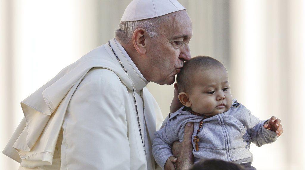 El papa Francisco besa a un niño a su llegada a la Plaza de San Pedro a bordo del papamóvil para su audiencia general semanal, en el Vaticano, el 10 de octubre de 2018. (AP Foto/Gregorio Borgia)