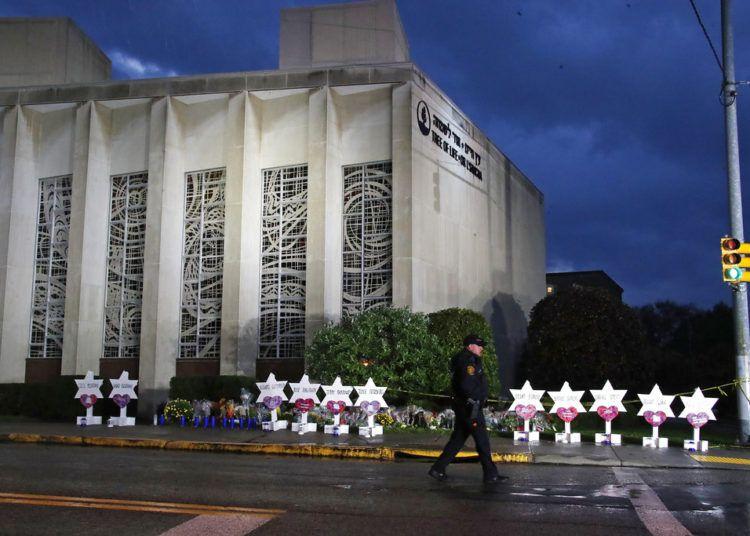 Un policía de Pittsburgh camina junto a la sinagoga Árbol de la Vida y una serie de flores y estrellas colocados en memoria de las víctimas de un hombre que se puso a disparar en el interior, el domingo 28 de octubre de 2018. Foto: Gene J. Puskar / AP.