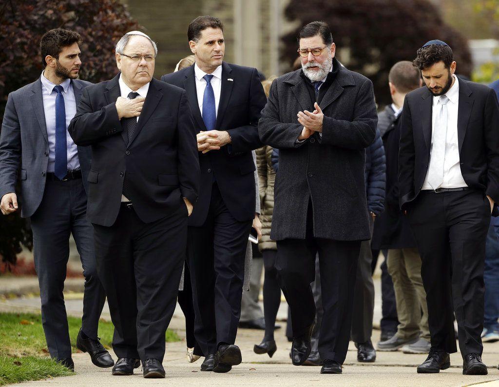 Bill Peduto, alcalde de Pittsburgh, segundo de derecha a izquierda, y el embajador israelí en Estados Unidos, Ron Dermer, tercero desde la derecha, caminan cerca de la sinagoga Árbol de la Vida en Pittsburgh, el domingo 28 de octubre de 2018, al día siguiente de una masacre allí Foto: Matt Rourke / AP.