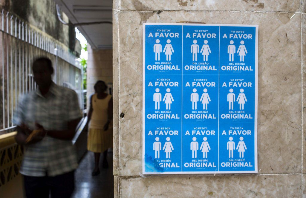 """Cartel con símbolos de parejas heterosexuales colocado en el exterior de una iglesia de la Liga Evangélica con el lema """"Yo estoy a favor del diseño original"""", contra la legalización de los matrimonios entre homosexuales en Cuba. Foto: Desmond Boylan / AP."""