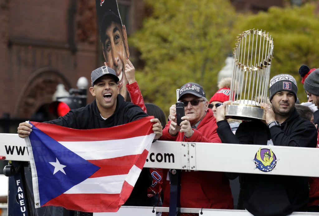 El manager Alex Cora exhibe la bandera de Puerto Rico durante el desfile de celebración en Boston. (AP Foto/Elise Amendola)
