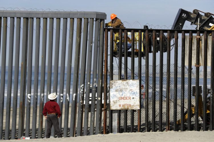 Un hombre en el lado estadounidense de la frontera (arriba) trabaja en la estructura ante la mirada de otro desde la playa, en Tijuana, México, el 15 de noviembre de 2018. (AP Foto/Gregory Bull)