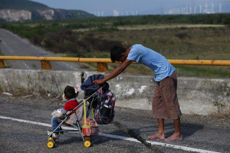 Un migrante empuja un carro de bebé por una carretera mientras una caravana formada por miles de centroamericanos sigue su lento avance hacia la frontera con Estados Unidos, entre Niltepec y Juchitan, en el estado de Oaxaca, México, el 30 de octubre de 2018. (AP Foto/Rebecca Blackwell)