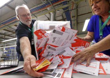 Los trabajadores electorales Mark Bezanson (izquierda) y Julie Olson arrojan sobre una mesa boletas de voto anticipado en la oficina electoral del condado de King, en Renton, Washington, el 5 de noviembre de 2018. Los votantes de Washington votan todos por correo. Foto: Elaine Thompson / AP.