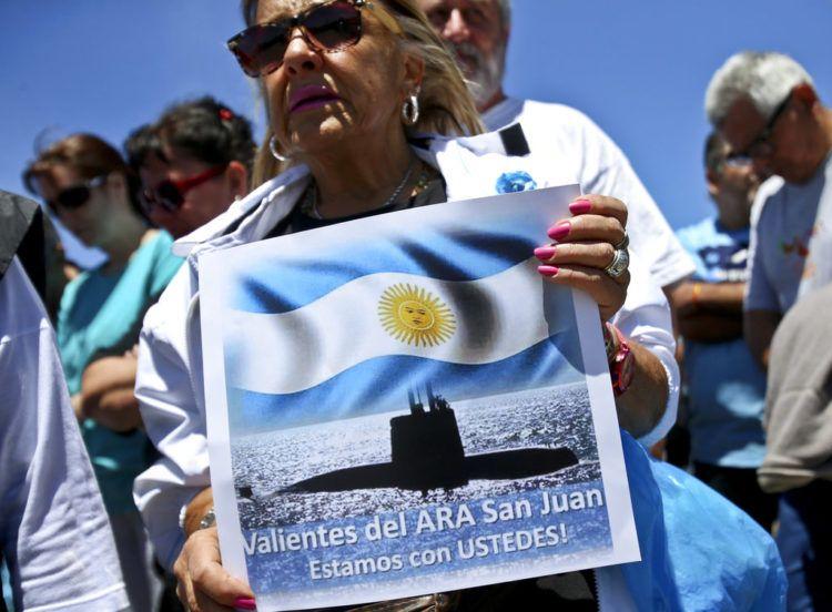 """En esta imagen de archivo, tomada el 25 de noviembre de 2017, una mujer sostiene un cartel con el mensaje """"Valientes del ARA San Juan, estamos con ustedes"""", delante de la base naval de la Armada en Mar del Plata, Argentina, donde se reunieron los familiares de los tripulantes desaparecidos en el sumergible. Foto: Esteban Félix / AP / Archivo."""