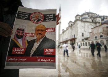 """Un hombre sostiene un cartel que muestra imágenes del príncipe heredero saudí Muhammed bin Salman y del periodista Jamal Khashoggi, en el que se describe al príncipe como """"asesino"""" y a Khashoggi como """"mártir"""" durante un momento de oración por Khashoggi, asesinado en el consulado saudí el mes pasado en Estambul, el viernes 16 de noviembre de 2018. Foto: Emrah Gurel / AP."""