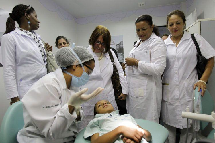 Médicos cubanos observan un procedimiento dental durante una sesión de capacitación en una clínica de salud en Brasilia. El gobierno de Brasil dice que va a comenzar pronto a seleccionar médicos locales para remplazar a los más de 8.000 doctores cubanos que trabajan en áreas del país donde los servicios médicos escasean. Foto> Eraldo Peres / AP.