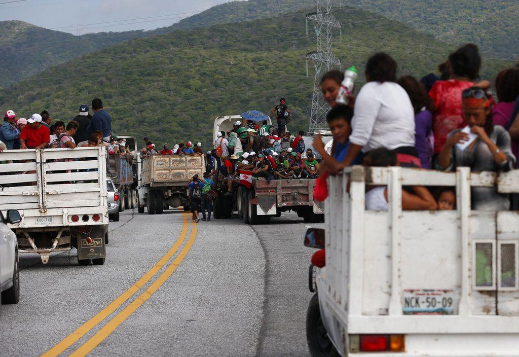 Migrantes se suben a las partes traseras de camiones mientras una caravana de miles de centroamericanos que esperan llegar a la frontera de Estados Unidos avanza desde Juchitán en el estado de Oaxaca, México, el jueves 1 de noviembre de 2018.  (AP Foto / Rebecca Blackwell)